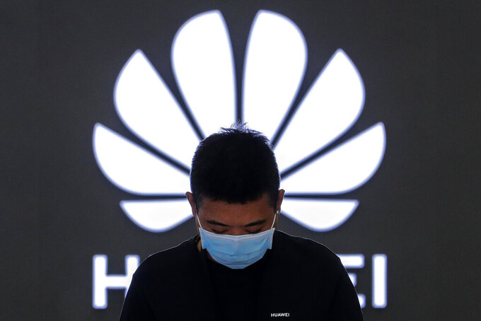 FILE - In this Aug. 31, 2020, file photo, an employee wearing a face mask to help curb the spread of the coronavirus stands inside a Huawei flagship store in Beijing. Chinese telecommunications equipment firm Huawei said Monday, April 12, 2021, that it has reached an agreement with HSBC in Hong Kong to obtain documents that its chief financial office Meng Wanzhou hopes will help prevent her extradition to the U.S.(AP Photo/Andy Wong, File)