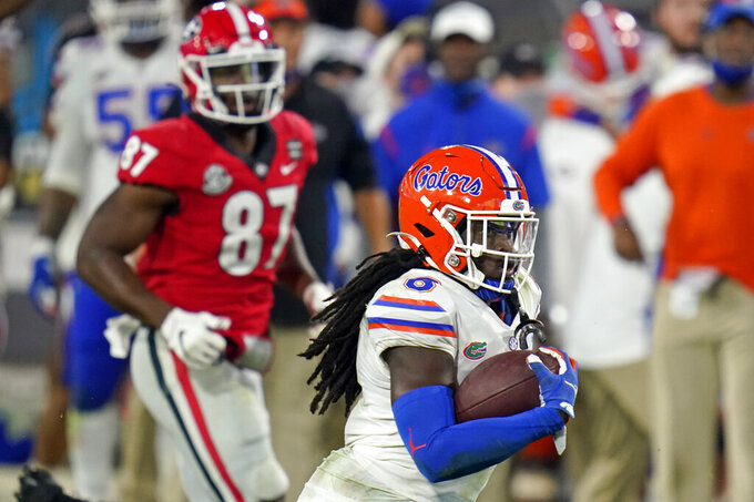 Florida defensive back Shawn Davis (6) runs past Georgia tight end Tre' McKitty (87) after he intercepted a pass during the second half of an NCAA college football game Saturday, Nov. 7, 2020, in Jacksonville, Fla. (AP Photo/John Raoux)