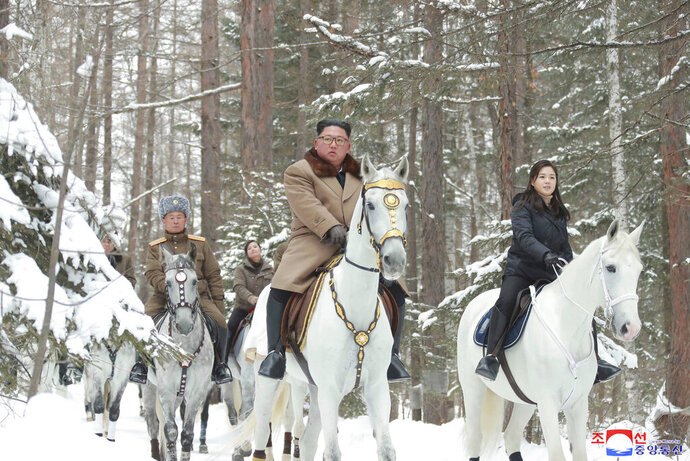 ADD KIM'S WIFE RI SOL JU AT RIGHT - This undated photo provided on Wednesday, Dec. 4, 2019, by the North Korean government shows North Korean leader Kim Jong Un, center, with his wife Ri Sol Ju, right, riding on white horse during his visit to Mount Paektu, North Korea. North Korea says leader Kim has taken a second ride on a white horse to a sacred mountain in less than two months. Independent journalists were not given access to cover the event depicted in this image distributed by the North Korean government. The content of this image is as provided and cannot be independently verified. Korean language watermark on image as provided by source reads: