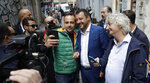 Italian Interior Minister and Deputy-Premier, Matteo Salvini, center-right, takes a selfie as he arrives for a press conference at the foreign press association in Milan, Italy, Friday, May 17, 2019. (AP Photo/Luca Bruno)