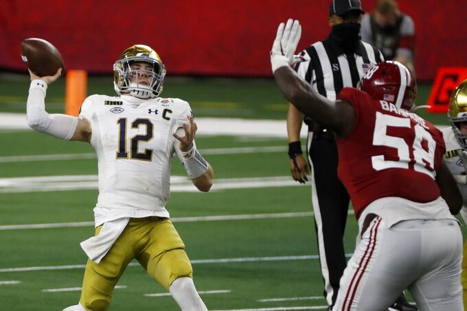 Notre Dame quarterback Ian Book (12) throws a pass under pressure from Alabama defensive lineman Christian Barmore (58) in the first half of the Rose Bowl NCAA college football game in Arlington, Texas, Friday, Jan. 1, 2021. (AP Photo/Roger Steinman)
