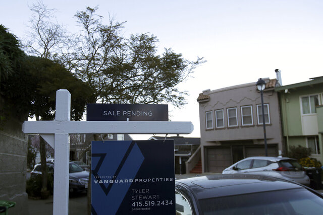 This Feb. 18, 2020, photo shows a sale pending real estate sign in front of homes in San Francisco. On Thursday, Feb. 27, the National Association of Realtors releases its January report on pending home sales, which are seen as a barometer of future purchases. (AP Photo/Jeff Chiu)