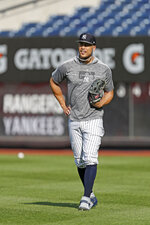 New York Yankees' Giancarlo Stanton, who has been out the much of the season with injuries and is still on the IL, stands in the outfield after a workout before the team's baseball game against the Texas Rangers, Wednesday, Sept. 4, 2019, in New York. (AP Photo/Kathy Willens)