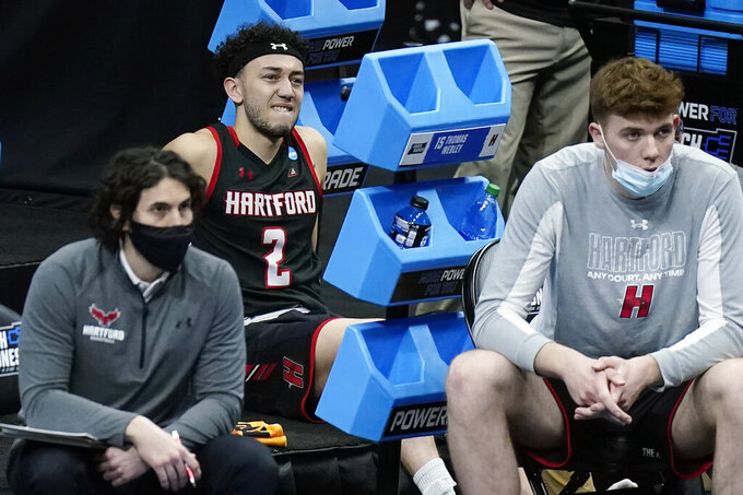 Hartford's D.J. Mitchell (2) watches from the bench after being injured during the first half of a college basketball game against Baylor in the first round of the NCAA tournament at Lucas Oil Stadium in Indianapolis Friday, March 19, 2021, in Indianapolis, Tenn. (AP Photo/Mark Humphrey)