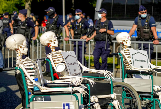 Medical stuff push skeletons in wheel chairs protesting in front of the Chancellery in Warsaw, Poland, Saturday, Sept.11, 2021. (AP Photo/Czarek Sokolowski)