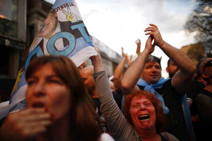 Supporters of center-left Peronist presidential candidate Alberto Fernández and running mate, former President Cristina Fernández, celebrate as they wait for election results outside their party's election headquarters in Buenos Aires, Argentina, Sunday, Oct. 27, 2019. Argentina faces a potentially sharp political shift on Sunday with center-left Peronist candidate Alberto Fernández favored to win an election dominated by frustration over an economic crisis that has eroded support for conservative incumbent Mauricio Macri. (AP Photo/Natacha Pisarenko)