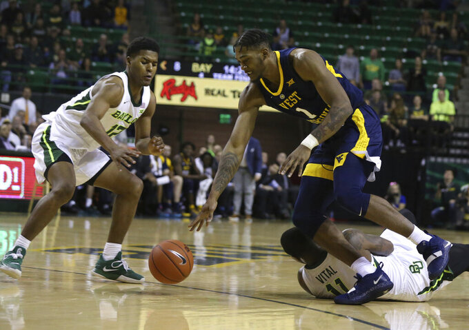 West Virginia forward Derek Culver, center, grabs a loose ball past Baylor guard Mark Vital, right, and Baylor guard Jared Butler, left, in the first half of an NCAA college basketball game, Saturday, Feb. 23, 2019, in Waco, Texas. (Rod Aydelotte//Waco Tribune-Herald via AP)