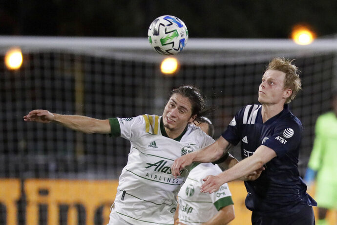 Portland Timbers defender Jorge Villafana, left, and New York City midfielder Gary Mackay-Steven battle for the ball during the second half of an MLS soccer match, Saturday, Aug. 1, 2020, in Kissimmee, Fla. (AP Photo/John Raoux)