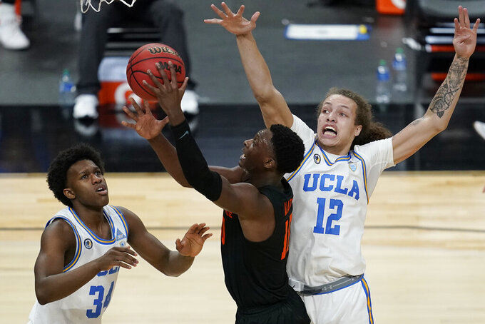 Oregon State's Warith Alatishe shoots around UCLA's David Singleton, left, and Mac Etienne (12) during the first half of an NCAA college basketball game in the quarterfinal round of the Pac-12 men's tournament Thursday, March 11, 2021, in Las Vegas. (AP Photo/John Locher)