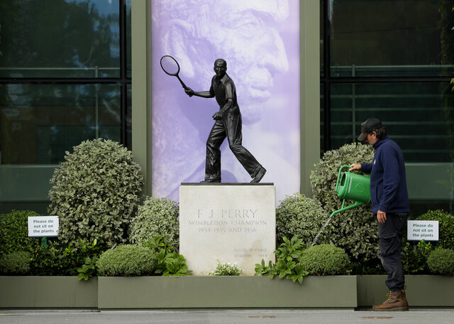 A gardener waters the plants alongside a statue of former Wimbledon Champion Fred Perry at the All England Lawn Tennis Club in Wimbledon in London, Monday, June 29, 2020.  The 2020 Wimbledon Tennis Championships, that were due to start today but have been cancelled due to the Coronavirus pandemic. (AP Photo/Kirsty Wigglesworth)