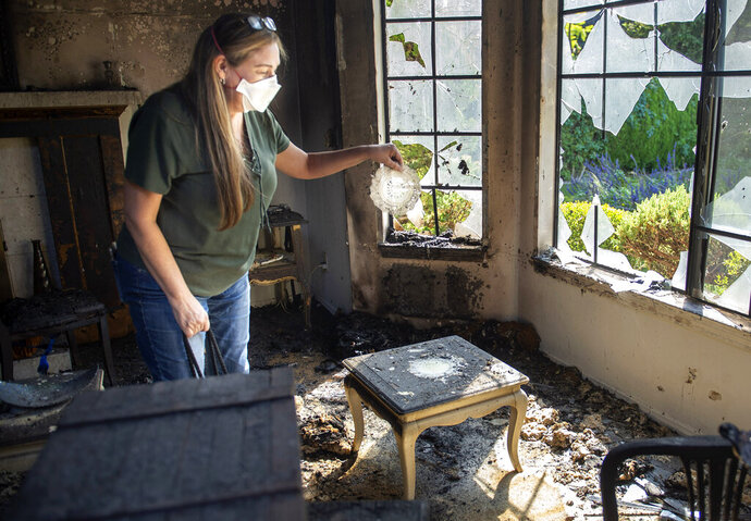 Loretta Reel picks up a doily that managed to survive a fire that destroyed her in-laws home in the Porter Ranch area of Los Angeles on Saturday, Oct. 12, 2019. (Mindy Schauer/The Orange County Register via AP)
