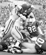 FILE - In this Oct. 8, 1978, file photo, New England Patriots Sam Cunningham (39) comes over the top of the Philadelphia line with some help from New England's Andy Johnson (32), to give the Patriots a 17-0 lead early in the second quarter of an NFL football game in Foxborough, Mass. Cunningham, an All-American fullback at Southern California whose performance against Alabama was credited for helping integrate football in the Deep South before he went on to a record-setting career with the New England Patriots, died Tuesday, Sept. 7, 2021, at his home in Inglewood, Calif., according to USC. He was 71.(AP Photo/David Tenenbaum, File)