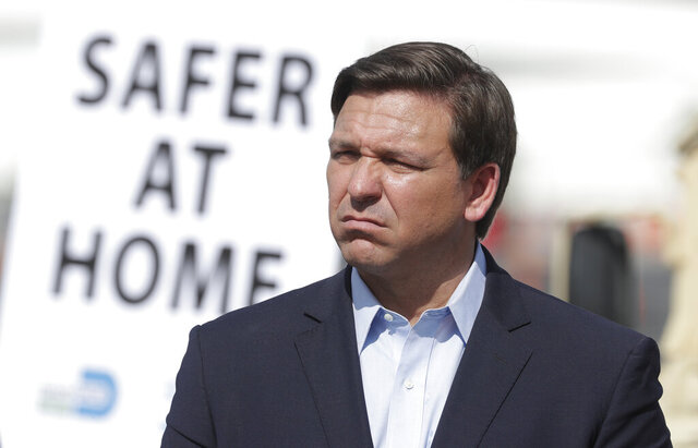 Florida Gov. Ron DeSantis listens during a news conference at a drive-through coronavirus testing site in front of Hard Rock Stadium, Monday, March 30, 2020, in Miami Gardens, Fla. Gov. Ron DeSantis doesn't want the people on the Holland America's Zandaam where four people died and others are sick to be treated in Florida, saying the state doesn't have the capacity to treat outsiders as the coronavirus outbreak spreads. (AP Photo/Wilfredo Lee)