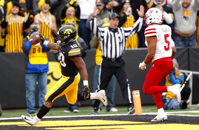 Iowa running back Mekhi Sargent, left, celebrates after catching a 5-yard touchdown pass in front of Nebraska linebacker Dedrick Young II during the second half of an NCAA college football game, Friday, Nov. 23, 2018, in Iowa City, Iowa. Iowa won 31-28. (AP Photo/Charlie Neibergall)