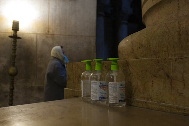 A woman attends mass next to three bottles of hand sanitizer available for worshippers at the Church of the Holy Sepulchre, where Jesus Christ is believed to be buried, during a third lockdown to curb the spread of the coronavirus, in the Old City of Jerusalem, Monday, Jan. 18, 2021. (AP Photo/Maya Alleruzzo)