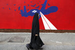 A woman walks past a new anti-U.S. mural on the wall of former U.S. embassy portraying the interception of Global Hawk US drone by Iran in Persian Gulf, after an unveiling ceremony in Tehran, Iran, Saturday, Nov. 2, 2019. Anti-U.S. works of graphics is the main theme of the wall murals painted by a team of artists ahead of the 40th anniversary of the takeover of the U.S. diplomatic post by revolutionary students. (AP Photo/Vahid Salemi)