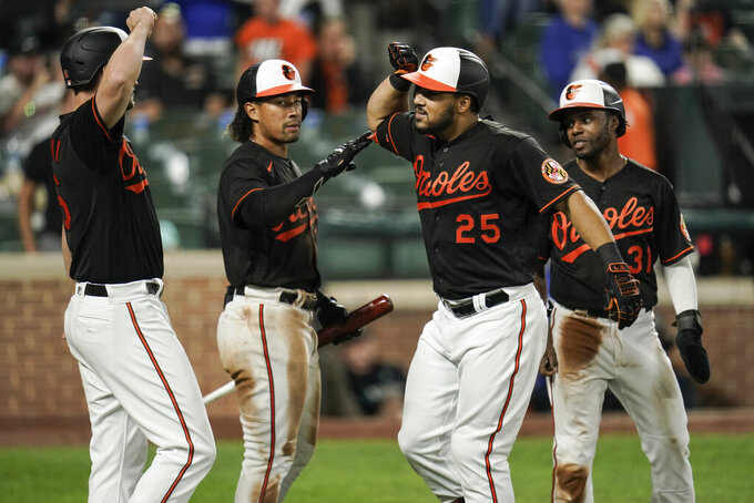 Baltimore Orioles' Anthony Santander, center, is greeted near home plate by Trey Mancini, left, Jahmai Jones, second from left, and Cedric Mullins after Santander hit a three-run home run off Toronto Blue Jays starting pitcher Julian Merryweather during the seventh inning of a baseball game, Friday, Sept. 10, 2021, in Baltimore. Mancini and Mullins scored on the home run. (AP Photo/Julio Cortez)