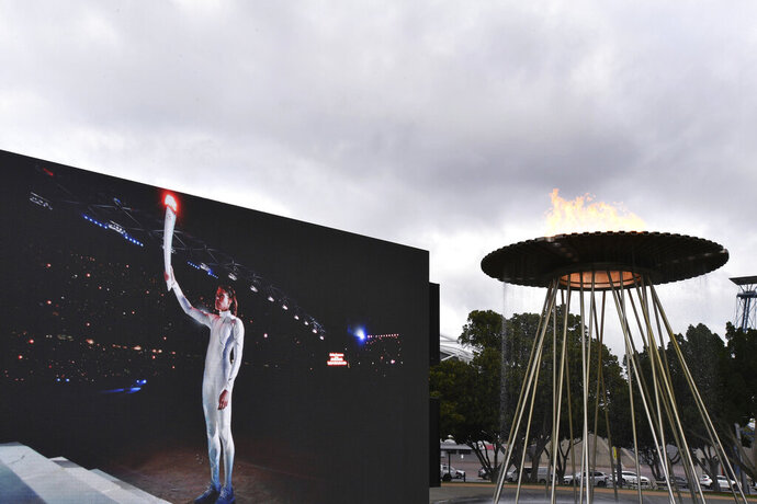 A video screen shows Cathy Freeman lighting the Olympic Cauldron as part of the 20th anniversary celebrations of the Sydney 2000 Olympic Games in Sydney, Tuesday, Sept. 15, 2020. Freeman, who lit the cauldron at the original opening ceremony and won the 400-meter race at the track in one of the country's all-time great sporting moments, said it was a wonderful gesture to have