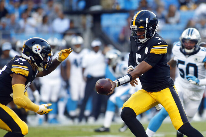 Pittsburgh Steelers quarterback Joshua Dobbs (5) hands off to running back Benny Snell (24) during the first half of an NFL preseason football game against the Carolina Panthers in Charlotte, N.C., Thursday, Aug. 29, 2019. (AP Photo/Brian Blanco)
