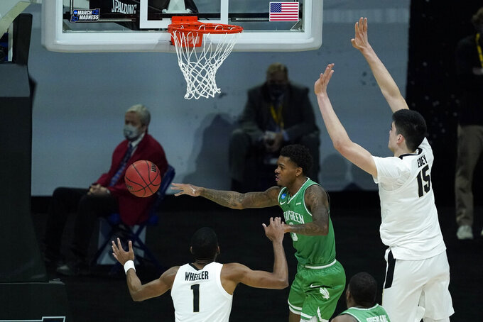 North Texas's Javion Hamlet (3) makes a pass against Purdue's Aaron Wheeler (1) and Zach Edey (15) during the first half of a first-round game in the NCAA men's college basketball tournament at Lucas Oil Stadium, Friday, March 19, 2021, in Indianapolis. (AP Photo/Darron Cummings)