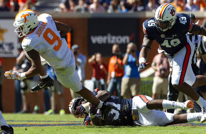 Auburn linebacker Chandler Wooten (31) grabs Tennessee running back Tim Jordan (9) during the first half of an NCAA college football game, Saturday, Oct. 13, 2018, in Auburn, Ala. Auburn linebacker Darrell Williams (49) trails on the play. (AP Photo/Vasha Hunt)