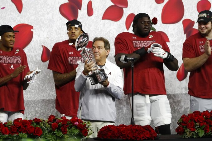Alabama head coach Nick Saban holds the trophy after their win against Notre Dame in the Rose Bowl NCAA college football game in Arlington, Texas, Friday, Jan. 1, 2021. (AP Photo/Roger Steinman)