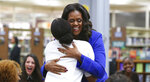 Former first lady Michelle Obama embraces a student at her alma mater, Whitney M. Young Magnet High School, on Chicago's West Side, Monday, Nov. 12, 2018, a day before the launch of a book tour to promote her memoir,