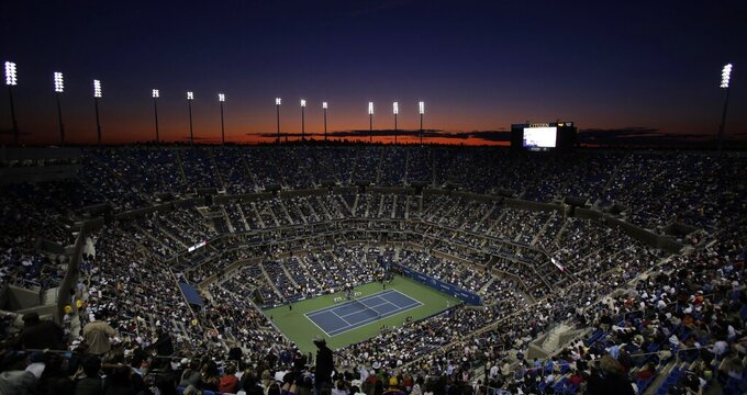 """FILE - In this Aug. 31, 2009, file photo, the sun sets over the skyline of New York and Arthur Ashe Stadium during the opening night of the U.S. Open tennis tournament in New York. The men's professional tennis tour is surveying players on LGBTQ issues. ATP CEO Massimo Calvelli tells The Associated Press it is part of a """"broader initiative"""" to create """"an environment for players and staff that is inclusive, that is diverse and that is very safe and welcoming."""" (AP Photo/Amy Sancetta, File)"""