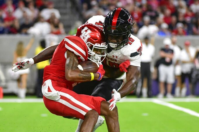 Houston wide receiver Nathaniel Dell (1) is tackled by Texas Tech linebacker Derrick Lewis II (48) during the second half of an NCAA college football game Saturday, Sept. 4, 2021, in Houston. (AP Photo/Justin Rex)