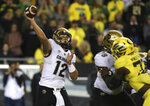 Colorado quarterback Steven Montez, left, throws a pass while under pressure from Oregon during the first quarter of an NCAA college football game Friday, Oct. 11, 2019, in Eugene, Ore. (AP Photo/Chris Pietsch)