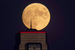 FILE - In this Wednesday, Sept. 30, 2020, file photo, a nearly full moon rises, with an office building in the foreground, in downtown Kansas City, Mo. The moon's shadowed, frigid nooks and crannies may hold frozen water in more places and in larger quantities than previously suspected, good news for astronauts at future lunar bases who could tap into these resources for drinking and making rocket fuel, scientists reported Monday, Oct. 26, 2020. (AP Photo/Charlie Riedel, File)