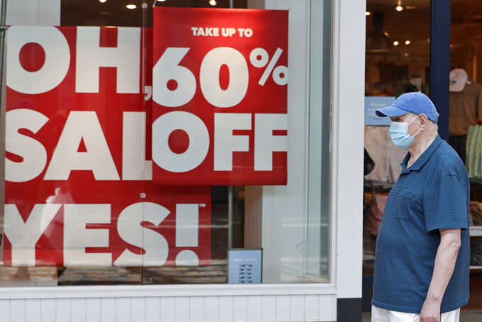 A man walks past a store with sale signs displayed at Great Lakes Mall, Wednesday, June 10, 2020, in Mentor, Ohio. Sales for retailers has plunged since the coronavirus pandemic. (AP Photo/Tony Dejak)
