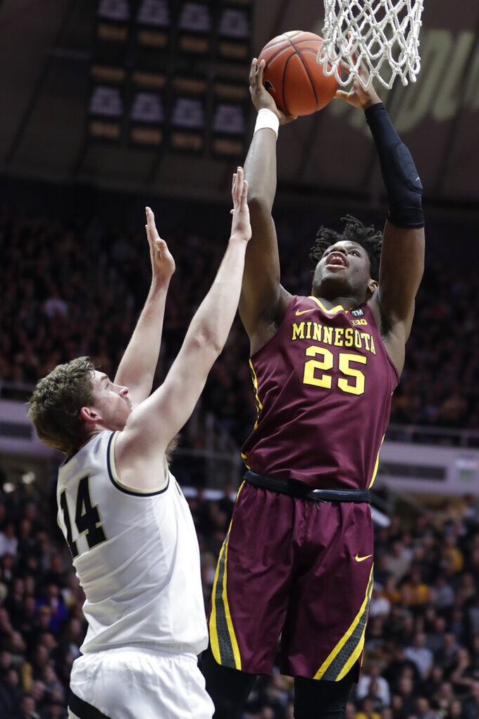 Minnesota center Daniel Oturu (25) shoots over Purdue guard Ryan Cline (14) during the first half of an NCAA college basketball game in West Lafayette, Ind., Sunday, Feb. 3, 2019. (AP Photo/Michael Conroy)