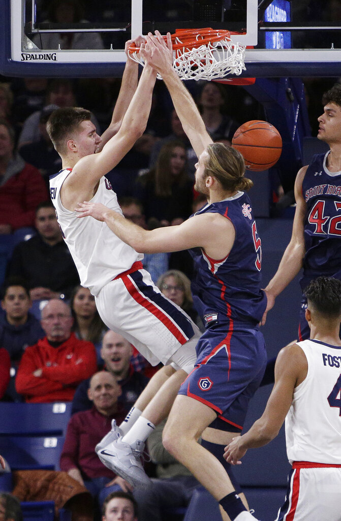 Gonzaga forward Filip Petrusev, left, dunks over Saint Mary's center Jock Perry during the second half of an NCAA college basketball game in Spokane, Wash., Saturday, Feb. 9, 2019. Gonzaga won 94-46. (AP Photo/Young Kwak)