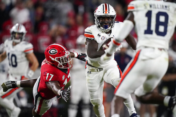 Georgia linebacker Nakobe Dean (17) dives to tackle Auburn running back Tank Bigsby during the first half of an NCAA college football game, Saturday, Oct. 3, 2020, in Athens, Ga. (AP Photo/Brynn Anderson)