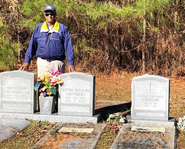 This Feb. 27, 2020 photo, Leon Saunders Jr. poses next to the gravestones of his mother and father in a cemetery behind Corinth Baptist Church in Jarvisburg., Va. (Jeff Hampton/The Virginian-Pilot via AP)