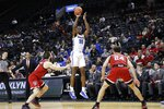 Memphis' Precious Achiuwa, center, shoots a three-point basket over North Carolina State's Braxton Beverly, left, and Devon Daniels during the first half of an NCAA college basketball game in the Barclays Classic, Thursday, Nov. 28, 2019, in New York. (AP Photo/Frank Franklin II)