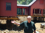 In this July 1, 2019 photo, Peter Brenn gestures toward his raised house in Willington, Conn. The concrete foundation of his home is being replaced with money from a state grant program. The foundation had been deteriorating due to the presence of an iron sulfide known as pyrrhotite, often described as