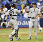 New York Yankees catcher Gary Sanchez (24) celebrates a 4-1 win over the Tampa Bay Rays with reliever Zach Britton at the end of a baseball game Monday, Sept. 24, 2018, in St. Petersburg, Fla. (AP Photo/Steve Nesius)