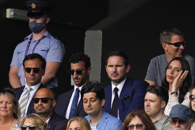 Former soccer player Frank Lampard, top second right, his wife Christine Lampard, right, Formula One driver Daniel Ricciardo, second left, watch the men's singles semifinals match on day eleven of the Wimbledon Tennis Championships in London, Friday, July 9, 2021. (AP Photo/Kirsty Wigglesworth)