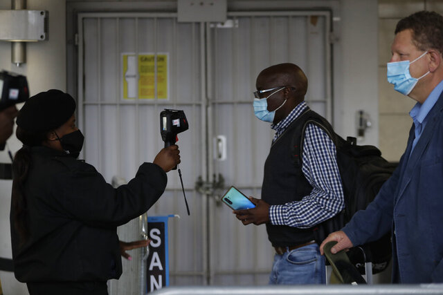Passengers have their temperatures taken at the International O.R. Tambo Airport in Johannesburg, Thursday, Oct. 1, 2020. South Africa has reopened to some international flights, ending a six-month ban on international travel that was part of its restrictions to combat the spread of COVID-19. (AP Photo/Themba Hadebe)