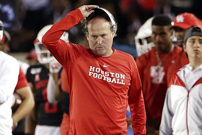 FILE - In this Oct. 24, 2019, file photo, Houston head coach Dana Holgorsen, center, reacts during the second half of an NCAA college football game against SMU, in Houston. In more than 25 years of coaching college football, Houston's Dana Holgorsen had to deal with only two games canceled before this season. This year alone, he and the Cougars have had five games either canceled or postponed because of the pandemic, pushing their season opener back again and again. (AP Photo/Michael Wyke, File)