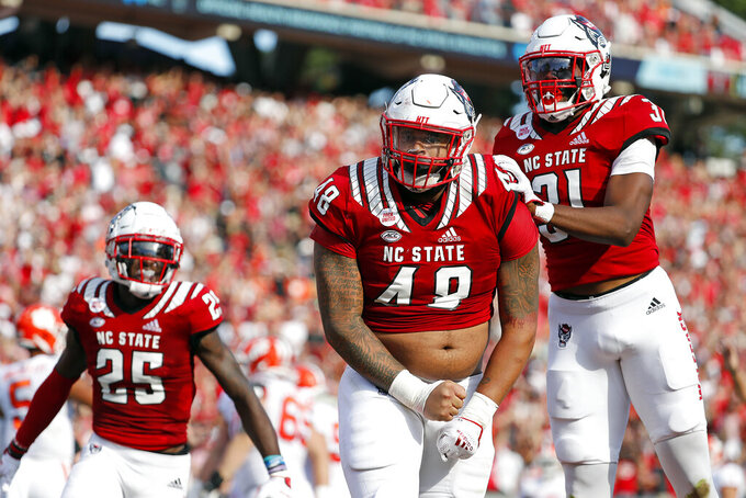 North Carolina State's Cory Durden (48) celebrates a sack with teammate Khalid Martin (21) and Shyheim Battle (25) during the first half of an NCAA college football game against Clemson in Raleigh, N.C., Saturday, Sept. 25, 2021. (AP Photo/Karl B DeBlaker)
