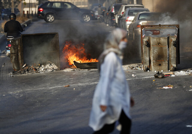 A woman passes in front of burned tires and garbage containers set on fire by anti-government protesters to block roads, during a protest against the economic crisis, in Beirut, Lebanon, Tuesday, June 30, 2020. Protesters closed several major roads in the Lebanese capital amid rising anger as the currency hit a new record low on the black market, electricity cuts increased and the government raised the price of bread for the first time in more than a decade. (AP Photo/Hussein Malla)