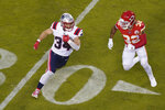 New England Patriots running back Rex Burkhead (34) runs from Kansas City Chiefs safety Tyrann Mathieu (32) during the first half of an NFL football game, Monday, Oct. 5, 2020, in Kansas City. (AP Photo/Charlie Riedel)
