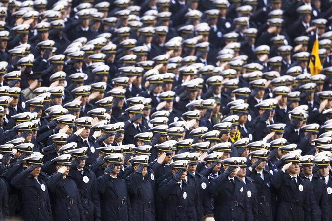 Navy midshipmen salute ahead of an NCAA college football game against Army, Saturday, Dec. 14, 2019, in Philadelphia. (AP Photo/Matt Slocum)