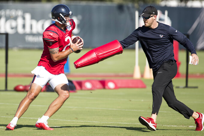 Houston Texans quarterback AJ McCarron (2) drops back to pass as he is chased by assistant quarterbacks coach T.J. Yates during an NFL training camp football practice Thursday, Aug. 20, 2020, in Houston. (Brett Coomer/Houston Chronicle via AP, Pool)