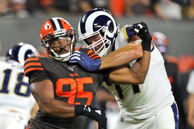 FILE - In this Sept. 22, 2019, file photo, Cleveland Browns defensive end Myles Garrett (95) tries to get past Los Angeles Rams offensive tackle Andrew Whitworth during the first half of an NFL football game in Cleveland. If teams are unable to hold offseason team workouts due to the coronavirus pandemic, Whitworth and Austin Blythe believe continuity and experience will be valuable commodities in the NFL this fall. That's one area where the Rams' offensive line should be much stronger this season. (AP Photo/David Richard, File)