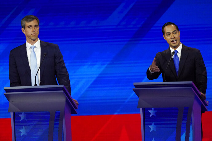 Former Texas Rep. Beto O'Rourke, left, listens as former Housing and Urban Development Secretary Julian Castro, right, responds to a question Thursday, Sept. 12, 2019, during a Democratic presidential primary debate hosted by ABC at Texas Southern University in Houston. (AP Photo/David J. Phillip)