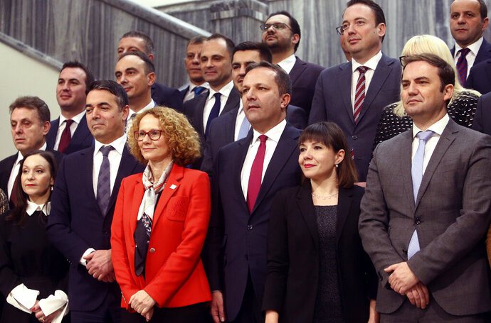 Oliver Spasovski, center front, the new prime minister of the caretaker government, and the members of the Cabinet pose for the media after the parliament voted in favor on a session in Skopje, North Macedonia, Friday, Jan. 3, 2020. The prime minister of North Macedonia Zoran Zaev submitted his resignation Friday, paving the way for a new caretaker Cabinet to be named in order to organize a snap election. (AP Photo/Boris Grdanoski)